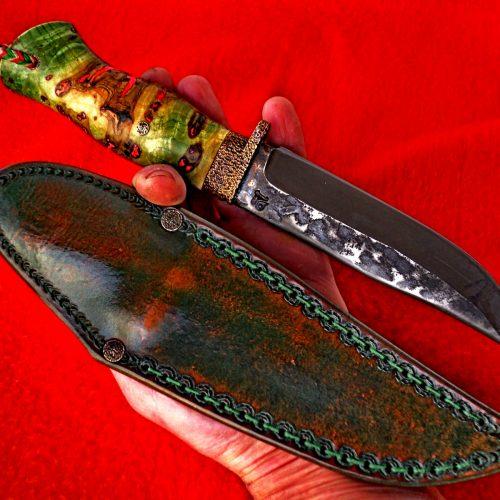 Нож 7   Изкован на огнище от стомана Х12МФ сьс рьзмери острие 140 на 30 на 4 мм ,Дрьжка от тумур сьс имплант светещ и дьлжина 115 мм.Канията е от твьрд гъон 3,5мм (   Не е наличен